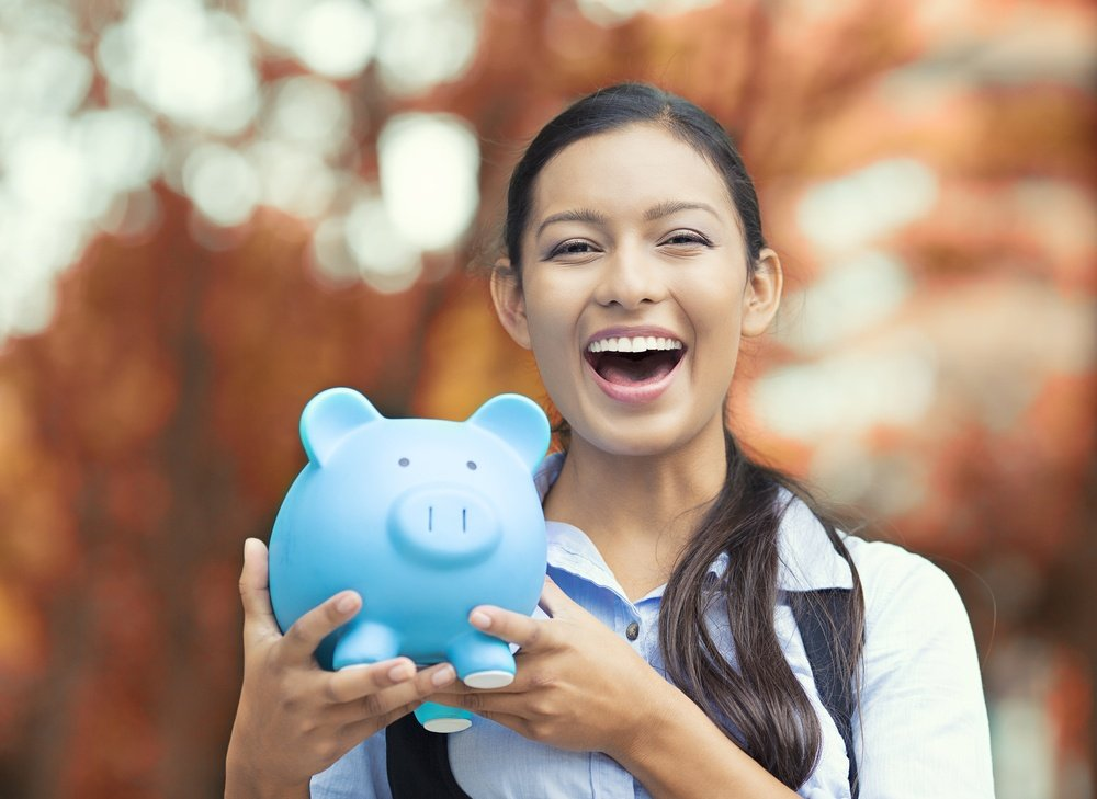 Closeup portrait happy, smiling business woman, bank employee holding piggy bank, isolated outdoors indian autumn background. Financial savings, banking concept. Positive emotions, face expressions.jpeg