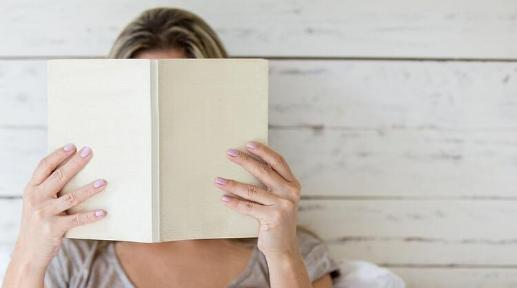 Woman reading a book and covering her face.jpeg